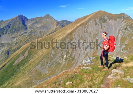 Backpacker woman standing on a mountain trail in sunny day of autumn - stock photo