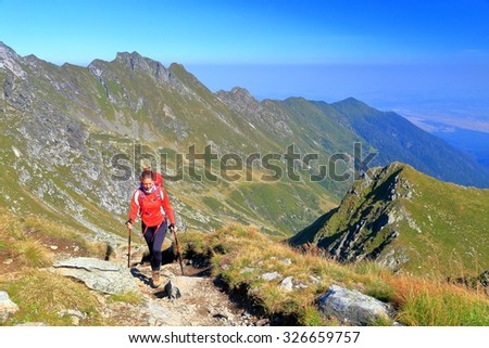 Backpacker woman walking a sunny trail on top of the mountain - stock photo