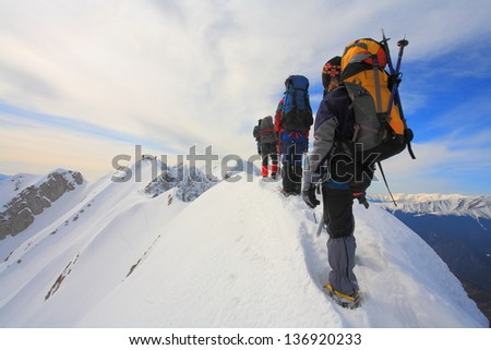 Backpackers climbing a mountain in winter - stock photo