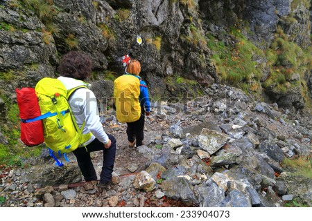 Backpackers descend a rocky trail a steep gully  - stock photo