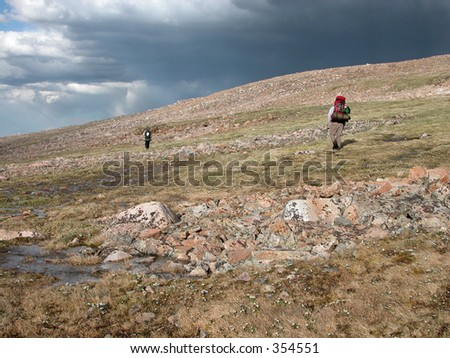 Backpackers escaping a thunderstorm on Froze-to-Death Plateau - stock photo