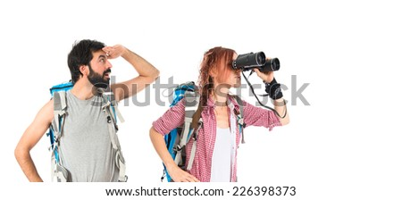 Backpackers with binoculars over isolated white background - stock photo