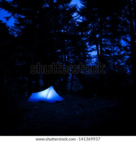 backpacking tent lit up at night. - stock photo