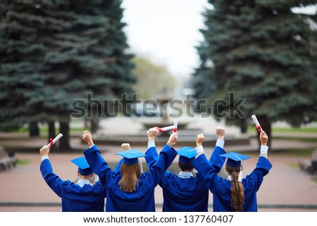 Backs of ecstatic students in graduation gowns holding diplomas - stock photo