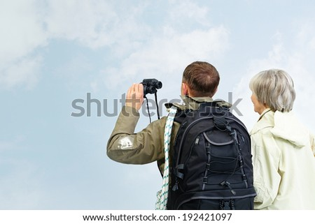 Backs of senior hikers with binoculars on trip - stock photo