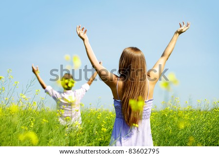 Backs of young couple with raised arms standing in flower field - stock photo