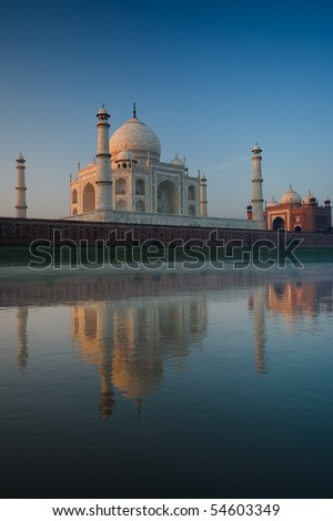 Backside of the majestic Taj Mahal and smaller red mosque glowing with reflected morning sunrise light in the calm rear Jamuna river on a clear blue sky day in Agra, India. Vertical copy space - stock photo