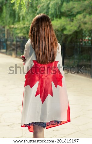 Backside view of young women wrapped around with Canada nation flag. - stock photo
