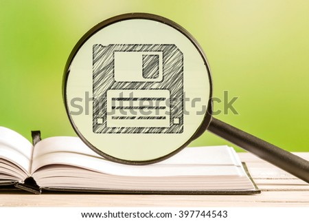 Backup information with a pencil drawing of a disk in a magnifying glass - stock photo