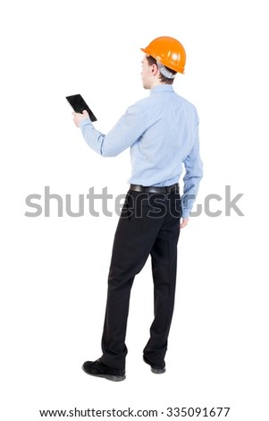 Backview business man in construction helmet stands and enjoys tablet or using a mobile phone. Standing young guy. Rear view people collection. backside view of person. Isolated over white background. - stock photo