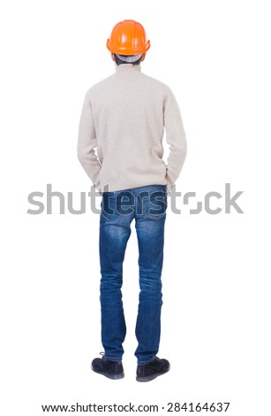 Backview of an engineer in construction helmet stands. Standing young guy. Rear view people collection.  Isolated over white background. Engineer in a warm jacket is folded his hands in his pockets. - stock photo