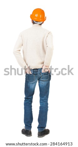 Backview of an engineer in construction helmet stands. Standing young guy. Rear view people collection.  backside view of person.  Engineer in a warm jacket is folded his hands in his back pockets. - stock photo