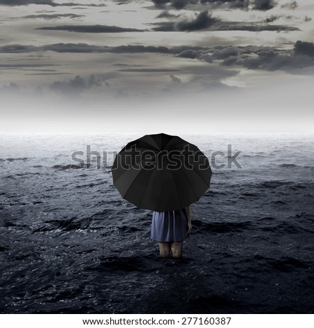 Backview of woman with umbrella alone at the sea - stock photo