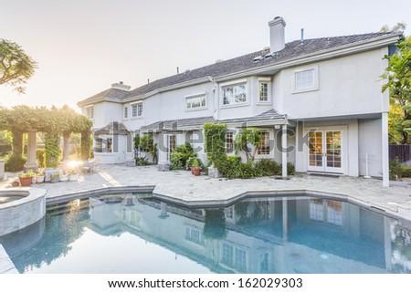 Backyard and swimming pool of luxury house - stock photo