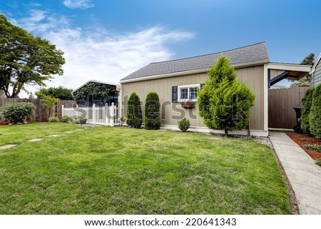 Backyard area with covered parking spot and shed. Backyard landscape design - stock photo