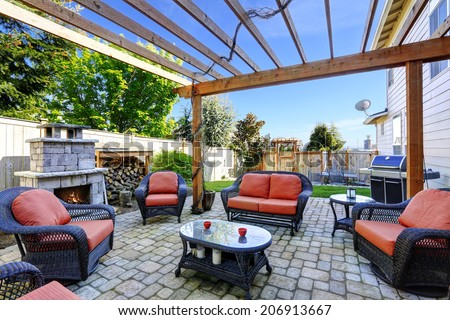 Backyard cozy patio area with wicker furniture set and  brick fireplace - stock photo