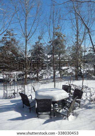 Backyard patio covered with a thick layer of snow on a bright winter day - stock photo