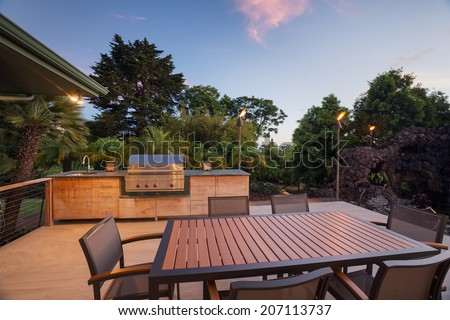 Backyard patio with BBQ grill and dining table on deck - stock photo