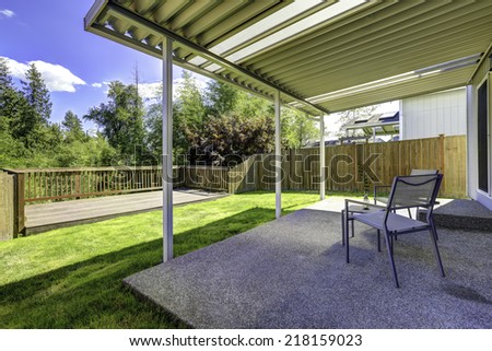 Backyard patio with concrete floor and wooden walkout deck with railings - stock photo