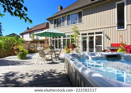 Backyard patio with  table set and jacuzzi - stock photo