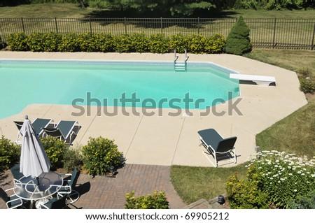 Backyard swimming pool with landscaped yard - stock photo