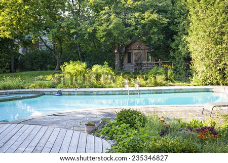 Backyard with garden, shed,  outdoor inground residential swimming pool, curved wooden deck and stone patio - stock photo