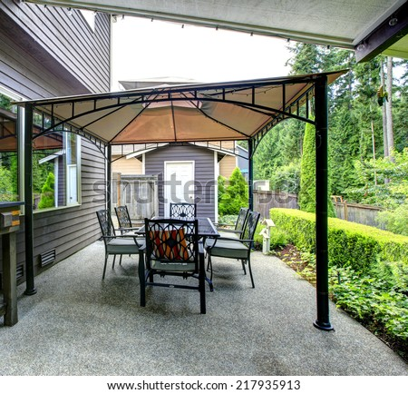 Backyard with gazebo, patio area and wooden cabinet with bottles - stock photo