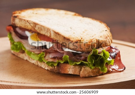 bacon and egg sandwich on wooden board - stock photo