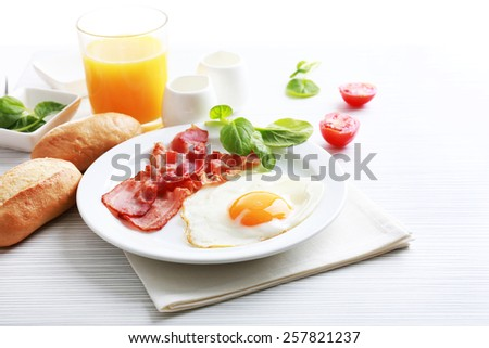 Bacon and eggs on color wooden table and white background - stock photo