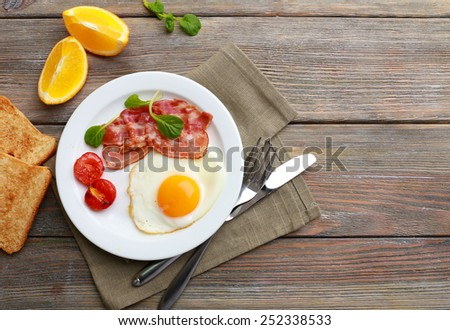 Bacon and eggs on rustic wooden planks background - stock photo