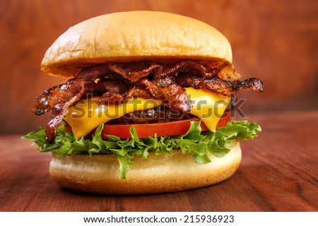 Bacon burger with beef patty on wooden table - stock photo