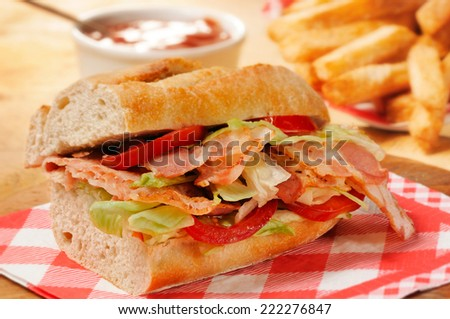 Bacon, lettuce and tomato (BLT) sandwich from freshly cut baguette on rustic wooden bread board. French fries and tomato ketchup on background. - stock photo