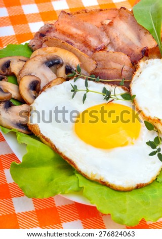 Bacon with sunny side up eggs served with toasts on a orange napkin - stock photo