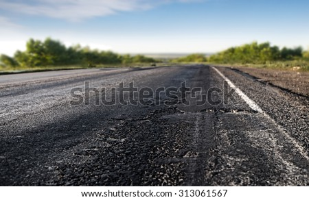 bad asphalt road through the green field and blue sky in summer day - stock photo