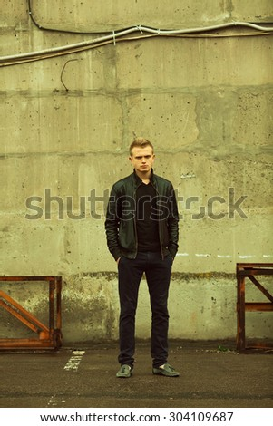 Bad boy concept. Full length portrait of brutal young man with short hair wearing black jacket, jeans and posing over urban background. Hands in pockets. Hipster style. Copy-space. Outdoor shot - stock photo