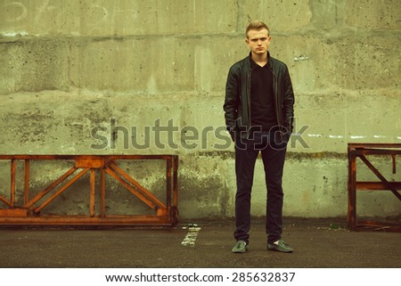 Bad boy concept. Portrait of brutal young man with short hair wearing black jacket, jeans and posing over urban background. Hands in pockets. Hipster style. Copy-space. Outdoor shot - stock photo