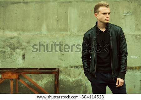 Bad boy concept. Portrait of brutal young man with short hair wearing black jacket, jeans and posing over urban background. Hand in pockets. Hipster style. Copy-space. Outdoor shot - stock photo