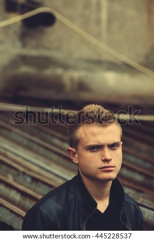 Bad boy concept. Portrait of brutal young man with short hair wearing black leather jacket, posing over urban corrugated background. Copy-space. Outdoor shot - stock photo