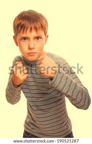 bad bully child boy blond  angry aggressive fights in striped shirt isolated on white background cross processing retro - stock photo