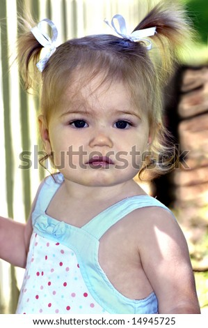 Bad day for small girl.  She is solemn faced and unhappy.  She is standing besides a picket fence. - stock photo
