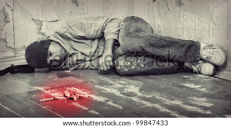 bad man - addict  with a syringe using drugs  lying on the floor - stock photo