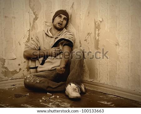 bad man - addict  with a syringe using drugs  sitting on the floor - stock photo