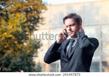 Bad news. Worried young businessman in suit and tie talking on the mobile phone while standing outdoors with office building in the background - stock photo