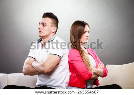 Bad relationship concept. Man and woman in disagreement. Young couple after quarrel sitting on sofa back to back - stock photo
