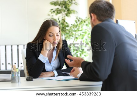 Bad salesman trying to convince to a bored client in her office or businessman in a job interview - stock photo