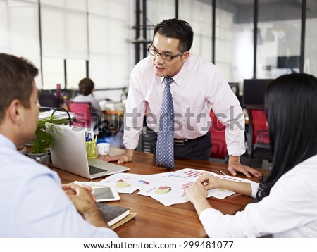 bad-tempered asian businessman yelling at two subordinates in office. - stock photo