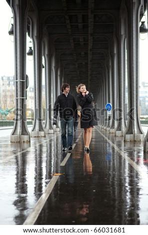 Bad weather in Paris. Couple on the Bir-Hakeim bridge at rain - stock photo