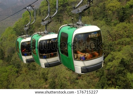 BADALING, CHINA - MAY 2, 2005:  Three cable car gondolas making their way up the steep mountainside to reach the Great Wall of China - stock photo