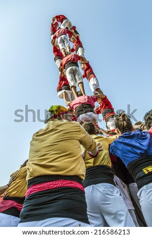 BADALONA, SPAIN - SEPTEMBER 11, 2014: Some unidentified people called Castellers do a Castell or Human Tower, typical tradition in Catalonia. Celebrating National Day the Catalan National - stock photo