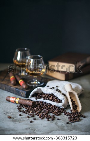 Bag of roasted coffee beans with cognac and cigars - stock photo